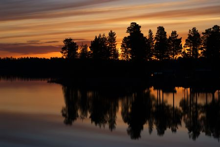 Sunset in swedish lapland reflecting in water photo