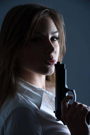 Beautiful woman blowing at her guns barrel Stock Photo - 4207658