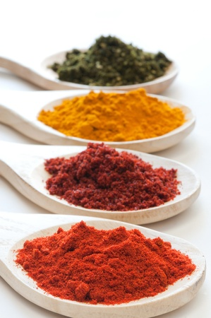 Various assorted spices in different colors on wooden spoons Stock Photo