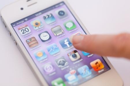 Stockholm, Schweden - 20. Mai 2012: A Womans Finger zeigt auf Facebook-Symbol auf dem iPhone 4. Gro�aufnahme von ihrem Finger, Icons und dem iPhone Homescreen. Das Mobiltelefon wird von Apple Computer, Inc. produziert