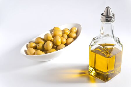 Bottle of olive oil and olives in a bowl Stock Photo