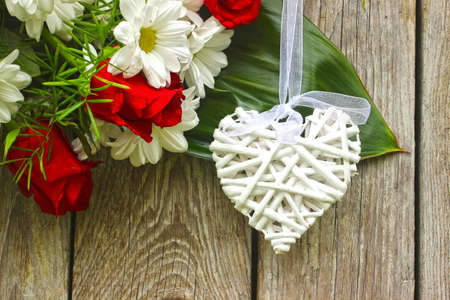 White wickers hearts and flowers on a wooden background