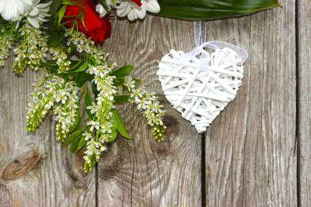 White wicker heart on a wooden background