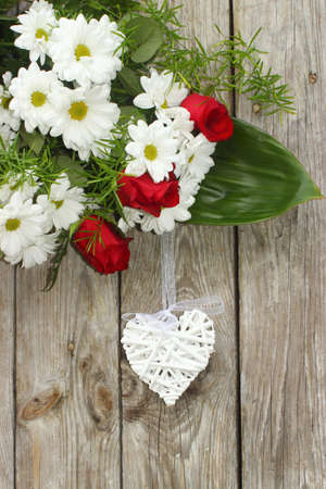 White wicker hearts and flowers on a wooden background Stock Photo