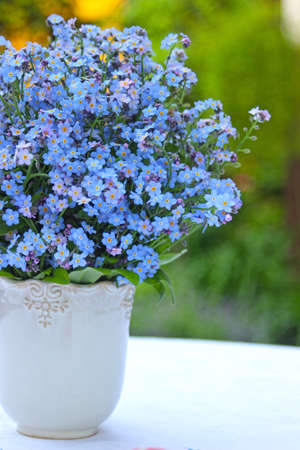 A bouquet of forget me not flowers in blue colors on the background