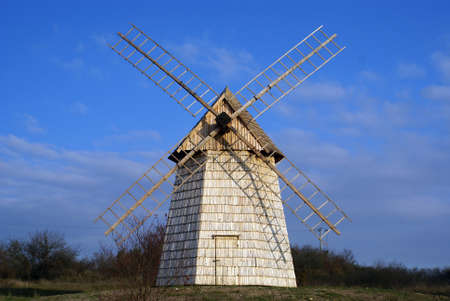 Old wooden windmill against the blue sky in the countryside