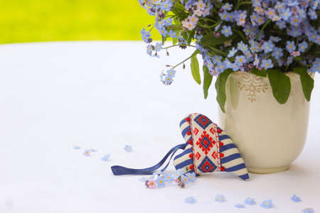 Heart in stripes and forget-me-nots on a white background
