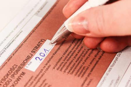 Hand Filling out Tax Form Foto de archivo