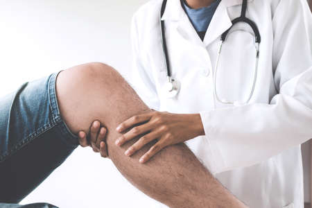 Lekarz sprawdzający pacjenta z kolanami w celu ustalenia przyczyny choroby.