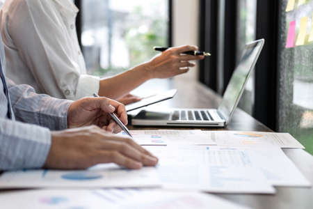 Businessman accountant and secretary making working audit and calculating expense financial annual financial report balance sheet statement, doing finance making notes on paper checking inspection. Stock Photo
