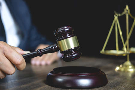 Legal law, advice and justice concept, male counseling lawyer or notary working on a documents and contract papers of the important case and wooden gavel, brass scale in courtroom. Stock Photo