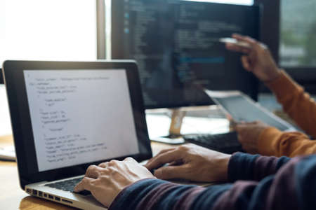 Professional Development programmer cooperating meeting and brainstorming and programming website working in a software and coding technology, writing codes and data code. Stock Photo