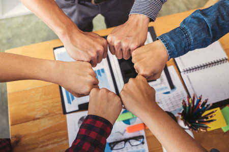 Teamwork of colleague assembly, Business team jointing putting fist together in circle as a connection meeting teamwork. Stock Photo