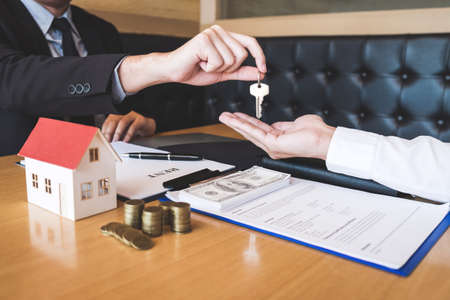 Estate agent giving house keys to client after signing agreement contract real estate with approved mortgage application form, concerning mortgage loan offer for and house insurance. Zdjęcie Seryjne