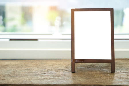 Mock up blank advertising whiteboard with easel standing on wood table in cafe and bar restaurant for display or montage of design space for text.