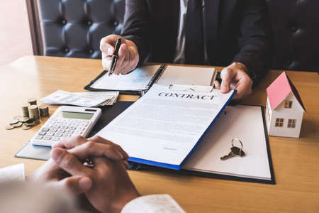 Estate agent broker giving pen to client signing agreement contract real estate with approved mortgage application form, buying or concerning mortgage loan offer for and house insurance.