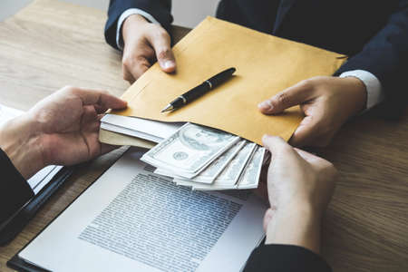Dishonest cheating in business illegal money, Business man giving bribe money in business people to accept agreement contract of investment deal, Bribery and corruption concept.