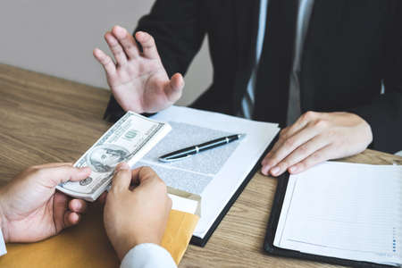 Anti bribery and corruption concept, Business man refusing and dont receive money banknote offered from business people to accept agreement contract of investment deal.