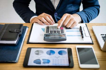 Mains d'homme d'affaires utilisant des informations textuelles sur une tablette numérique pour analyser les données des graphiques statistiques financiers et calculer le coût du projet d'investissement. Banque d'images