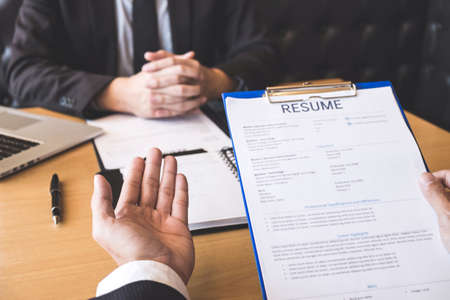 Employer or recruiter holding reading a resume during about his profile of candidate, employer in suit is conducting a job interview, manager resource employment and recruitment concept.