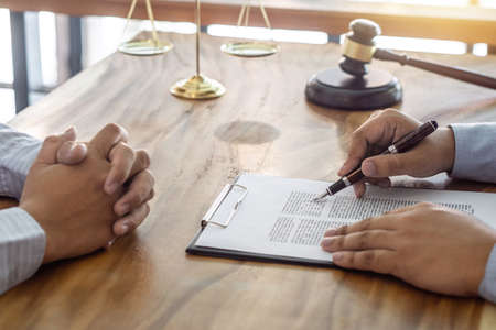 Law, lawyer attorney and justice concept, Consultation between a male lawyer and client, giving advice and prosecutions about the regarding real estate, report of the important case in the workplace. Stock Photo