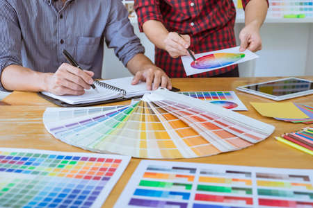 Team of Creative graphic designer meeting working on new project, choose selection color and drawing on graphics tablet with work tools and accessories.