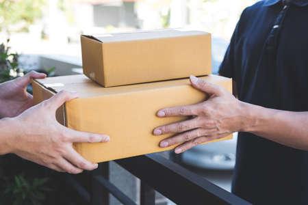 Hombre de correo de entrega que da la caja del paquete al destinatario, propietario joven que acepta el paquete de cajas de cartón del envío postal, mensajería a domicilio y concepto de la mente del servicio de entrega. Foto de archivo