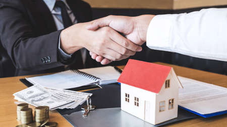 Image of successful deal of real estate, Broker and client shaking hands after signing contract approved application form, concerning mortgage loan offer for and house insurance. 写真素材