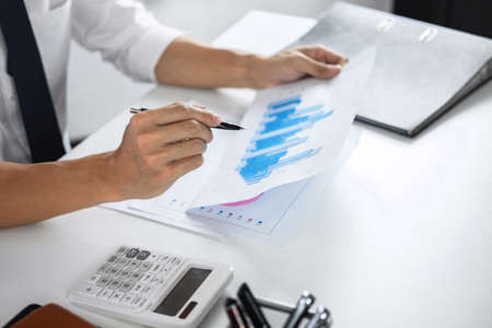Businessman accountant working audit and calculating expense financial data on graph documents, doing finance in workplace.