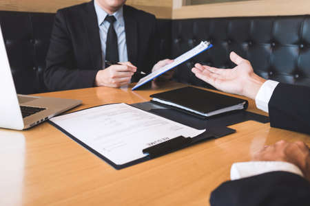 Employer arriving for a job interview, businessman listen to candidate answers explaining about his profile and colloquy dream job, manager sitting in job Interview talking in modern office. Foto de archivo