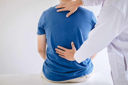 Doctor physiotherapist treating lower back pain patient after while giving exercising treatment on stretching in the clinic, Rehabilitation physiotherapy concept.