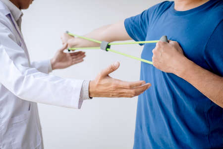 Doctor physiotherapist assisting a male patient while giving exercising treatment on stretching his arm with exercise band in the clinic, Rehabilitation physiotherapy concept.