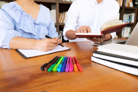 Tutor, learning, education, Group of young people learning studying lesson in library during helping teaching friend education prepare for exam, youth campus friendship teenager teens concept. 免版税图像