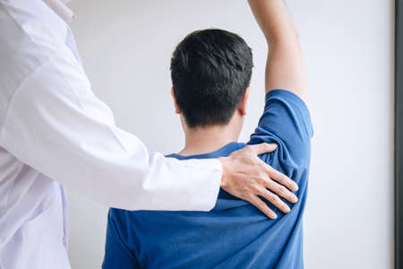 Doctor physiotherapist assisting a male patient while giving exercising treatment massaging the shoulder of patient in a physio room, rehabilitation physiotherapy concept.