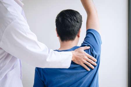 Médico fisioterapeuta que ayuda a un paciente masculino mientras da un tratamiento de ejercicio masajeando el hombro del paciente en una sala de fisioterapia, concepto de fisioterapia de rehabilitación. Foto de archivo