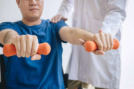 Doctor physiotherapist assisting a male patient while giving exercising treatment on stretching his arm with dumbbell in the clinic, Rehabilitation physiotherapy concept.