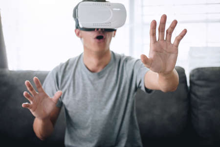 Young asian man having fun wearing playing virtual reality headset glasses to enjoying in holiday at home, 3D gadget technology, VR AR glasses.