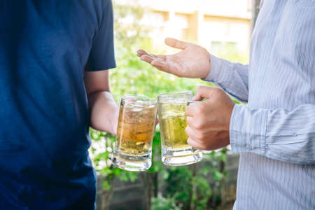 Two young man hand raise a glass of beer to celebrate the holiday festival happy drinking beer outdoors and enjoying at home. Imagens