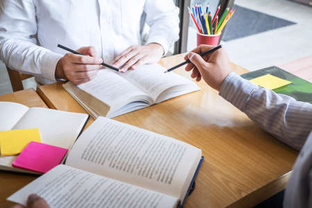 Group of young people learning studying new lesson to knowledge in library during helping teaching friend education prepare for exam, youth campus friendship teenager teens concept.