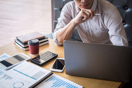 Businessman working investment project on laptop computer with report document and analyze, calculating financial data on graph documents, doing finance making statistics. Reklamní fotografie