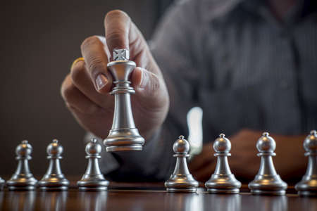 Gold and silver chess with player, Intelligent businessman playing chess game competition to planning business strategic to development for win and success.