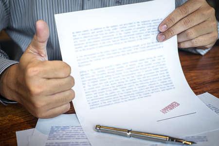 Sello de manos de empresario en documento de papel para aprobar acuerdo de contrato de inversión empresarial.
