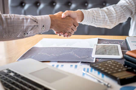 Finishing up a meeting, handshake of two happy business people after contract agreement to become a partner, collaborative teamwork. Imagens