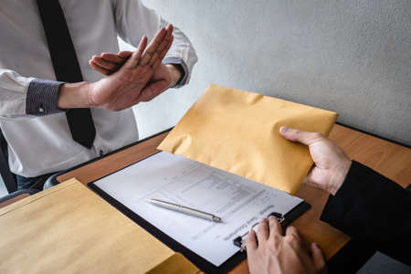 Anti bribery and corruption concept, Business man refusing and dont receive money banknote in envelop offer from business people to accept agreement contract of investment deal. Stock Photo