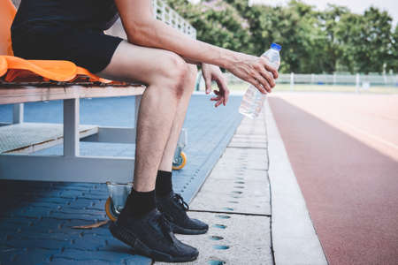 Young fitness athlete man resting on bench with bottle of water preparing to running on road track, exercise workout wellness concept. Stock Photo