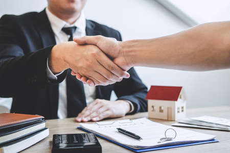 Finishing to successful deal of real estate, Broker and client shaking hands after signing contract approved application form, concerning mortgage loan offer for and house insurance.