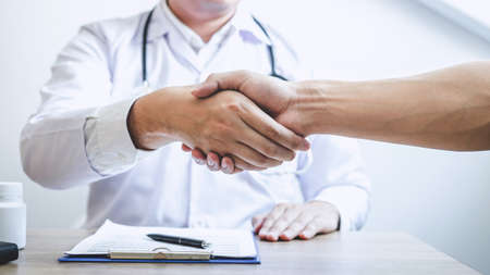 Doctor having shaking hands to congrats with patient after recommend treatment while discussing explaining his symptoms and counsel diagnosis health, healthcare and assistance concept. Imagens