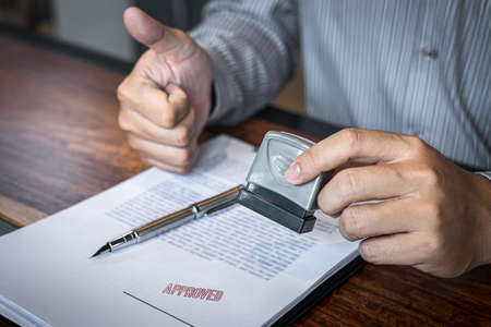 Hands of businessman stamp on paper document to approve business investment contract agreement.