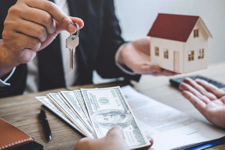 Estate agent broker receive money from client after signing agreement contract real estate with approved mortgage application form, buying or concerning mortgage loan offer for and house insurance.