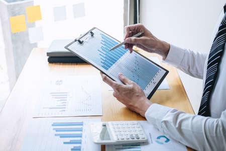 Contador de hombre de negocios que trabaja analizando y calculando el estado de cuenta del balance del informe financiero anual financiero de los gastos y analiza el gráfico y el diagrama del documento, haciendo las finanzas haciendo notas en el informe.